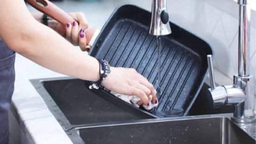 lady washing a grill pan in the sink