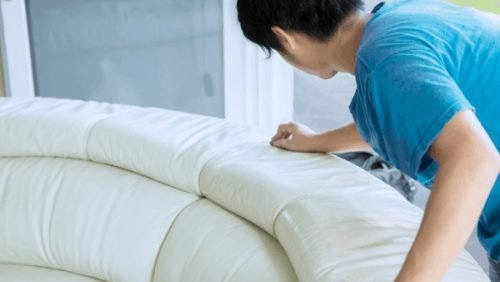 man cleaning couch with hands