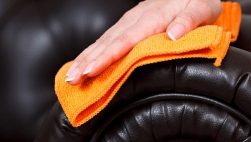manicured nails cleaning couch with orange coth