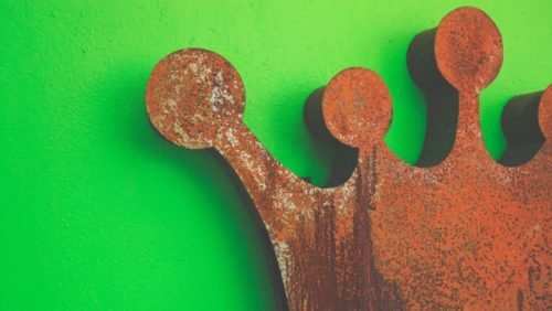rusty metal crown on green background